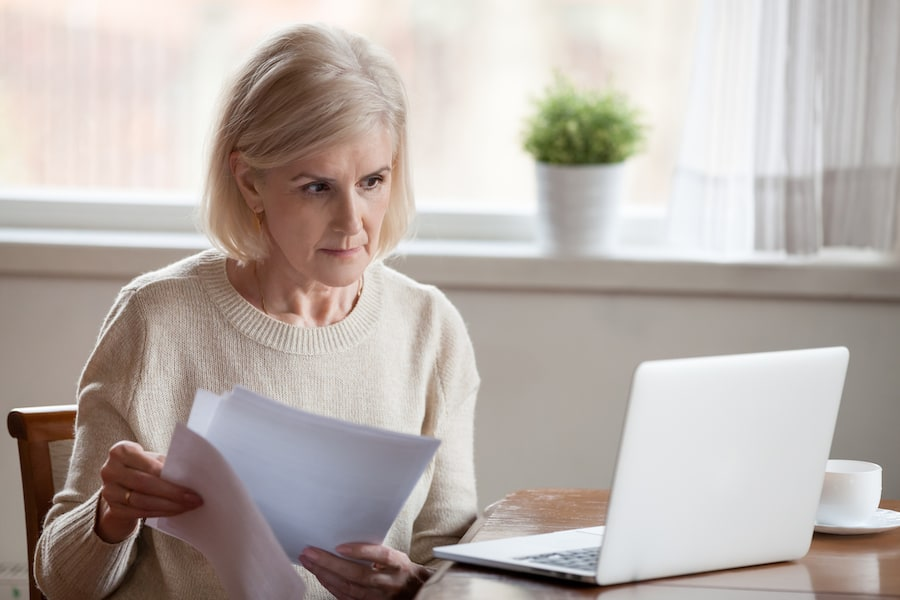 Woman using laptop holding papers