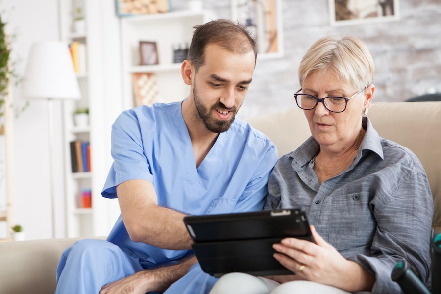 Healthcare worker helping senior woman use tablet