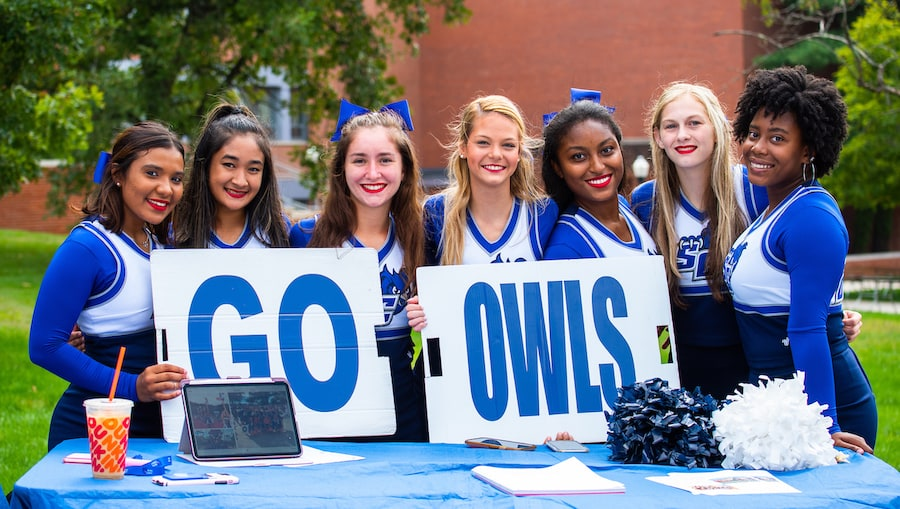 Cheerleaders holding a sign which says Go Owls