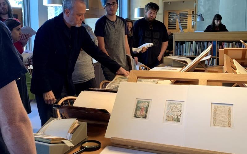 Professor Tony Rosso displaying William Blake's watercolors to Southern English majors
